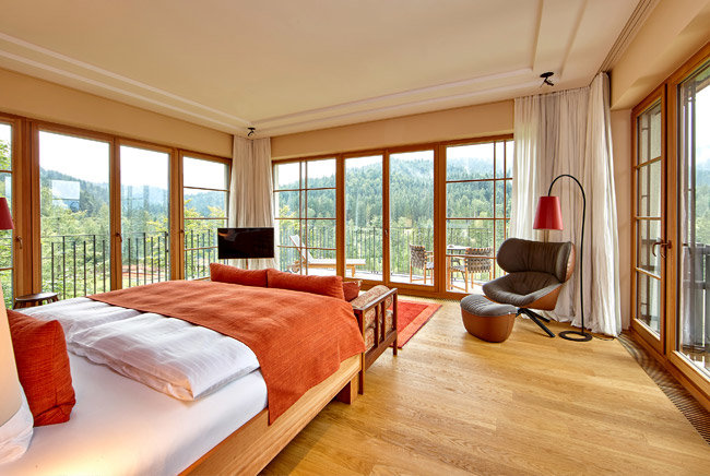 Hotel room in Schloss Elmau with bed and armchair and a clear view of the woods